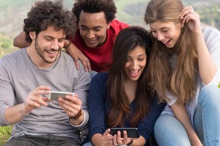 Gruppe Lachen Freunde mit Handy im Freien