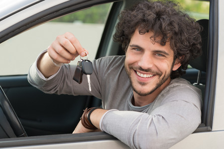 Portrait Of Young Happy Man Showing The Key Sitting In New Car photo