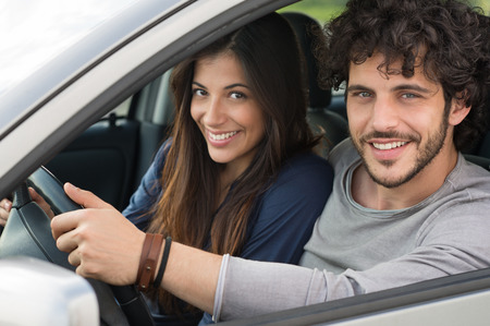 Happy Young Couple Sitting In Car Stock Photo