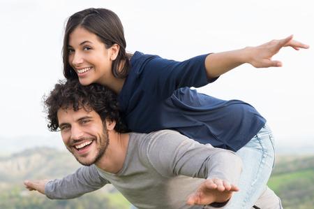 mujeres latinas: Retrato del hombre joven que lleva a cuestas a su novia al aire libre Foto de archivo