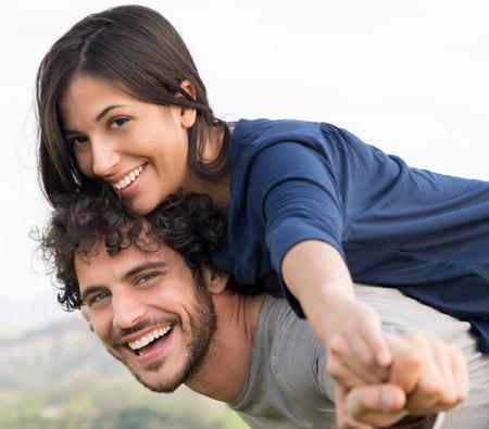 mujeres latinas: Joven hombre feliz que da a cuestas paseo a la mujer sonriente