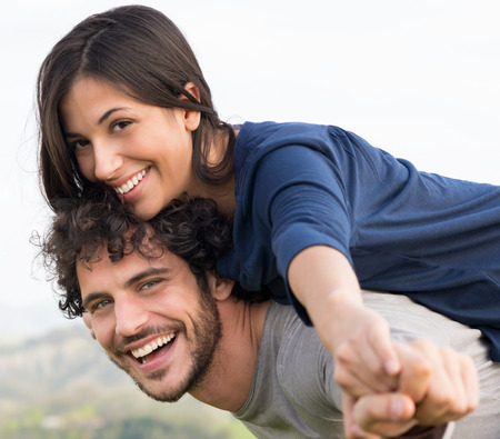 piggyback: Young Happy Man Giving Piggyback Ride To Smiling Woman