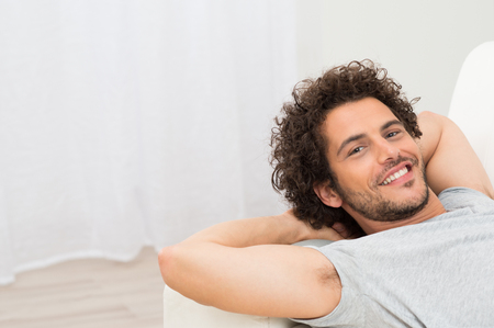 Portrait Of Happy Young Man Resting On Sofa photo