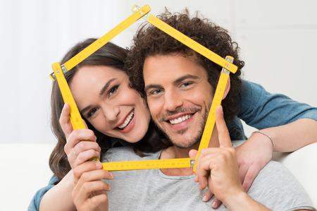 접는 눈금자와 집 모양을 만들기 행복 한 젊은 커플