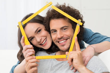 restore: Happy Young Couple Making House Shape With Folding Ruler Stock Photo