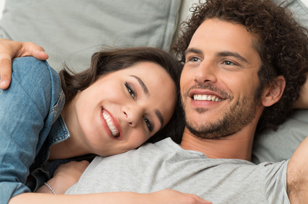 Cerca de la feliz pareja amorosa tumbado en el sofá