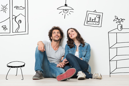 Portrait Of Happy Young Couple Sitting On Floor Looking Up While Dreaming Their New Home And Furnishing photo