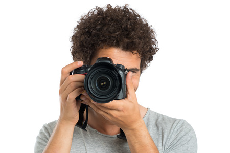 Young Man Taking Picture With Digital Camera Isolated On White Background photo
