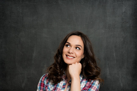Happy Young Woman Contemplating Over Gray Background photo