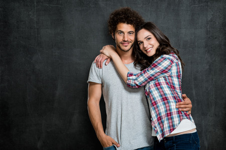 Portrait Of Beautiful Young Couple Over Blackboard