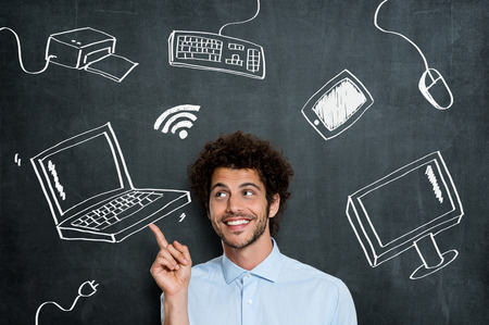 Portrait Of Young Man With Different Computer Technology Over Gray Background Stock Photo