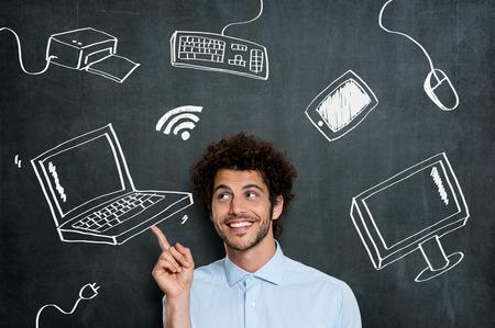 tecnologia: Ritratto Di Giovane Uomo Con Different Computer Technology su sfondo grigio