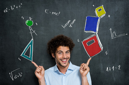 Portrait Of Happy Man Student With Books And Algebra Items Over A Blackboard photo