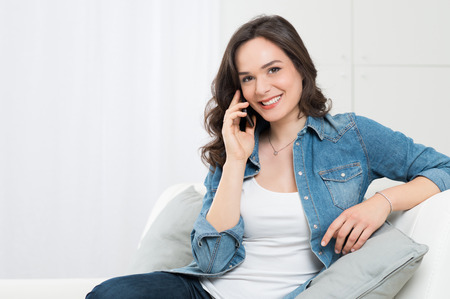 Smiling Young Woman Sitting On Couch Talking On Phone photo