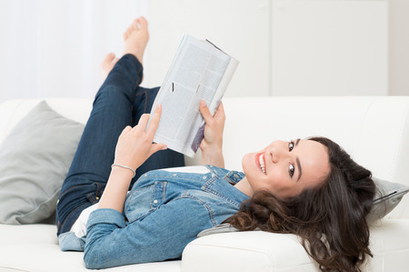 mujer alegre: Sonrisa feliz de la mujer que miente en el sofá leyendo una revista