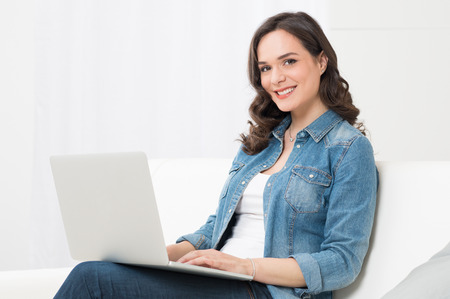 Portrait Of Happy Young Woman Sitting On Couch Using Laptop