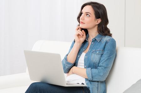 Doordachte jonge vrouw zittend op bank met laptop