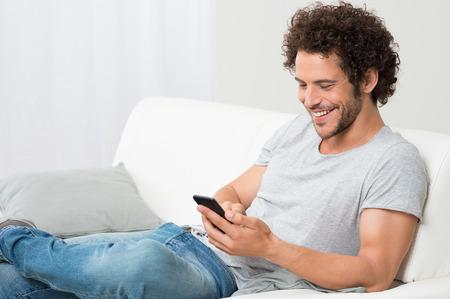 행복 한 젊은 남자가 소파에 편안하고 핸드폰을 찾고