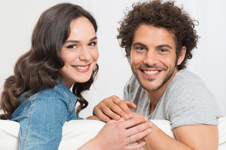 Portrait Of Happy Young Couple Sitting On Sofa photo
