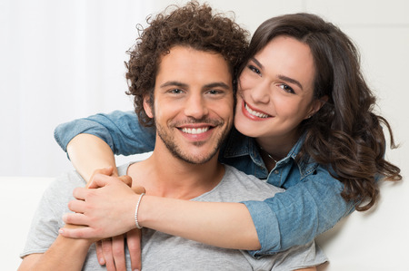 Portrait Of Young Woman Embracing Her Boyfriend From Behind Stock Photo