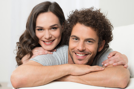 latin: Portrait Of Smiling Loving Young Couple Lying On Couch