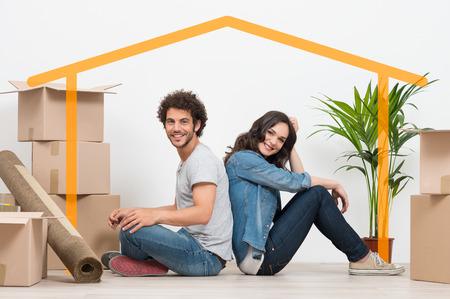 Sonriente pareja joven sentada de espaldas después de casa móvil