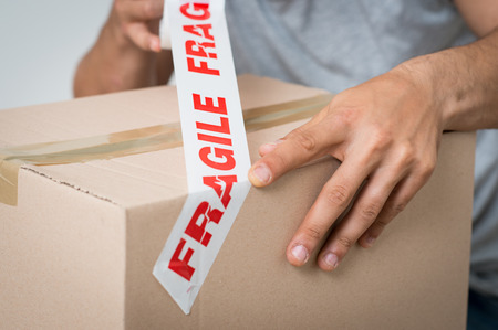 hand move: Close up Of A Man Packing Cardboard Box With tape