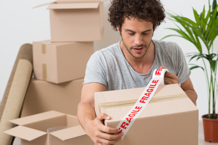 Portrait Of A Young Man Packing Cardboard Box With Fragile tape