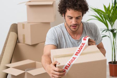 Portret Van Een Jonge Man Verpakking Kartonnen doos met Fragile tape
