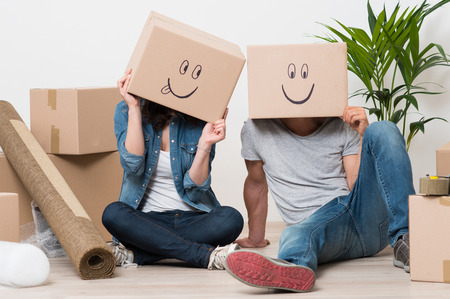 casa: Coppia con scatole di cartone sulla testa con Smiley si siede sul pavimento dopo la casa in movimento