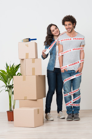 Smiling Woman Near Stack Of Boxes Wrapping Man With tape Stock Photo