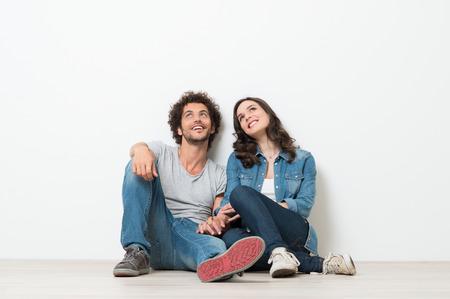 肖像画の幸せな若いカップル座って上床探してアップの準備ができてテキストまたは製品