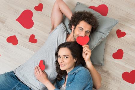 床に横たわって赤いハート一緒に保持している愛する若いカップル