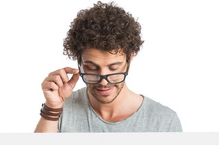 Cerca del hombre joven detrás del cartel de Mirar hacia abajo con gafas aisladas sobre fondo blanco
