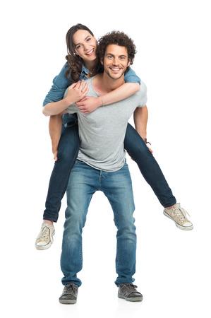 parejas enamoradas: Retrato del hombre joven que lleva a cuestas a su novia aislados en fondo blanco