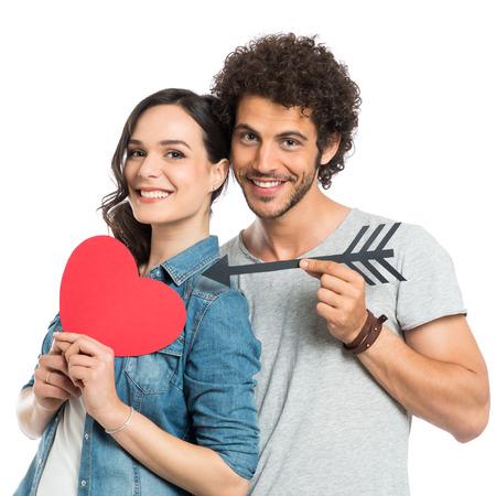 ležérní: Šťastný pár drží šipku a papír srdce izolované bílém pozadí Reklamní fotografie