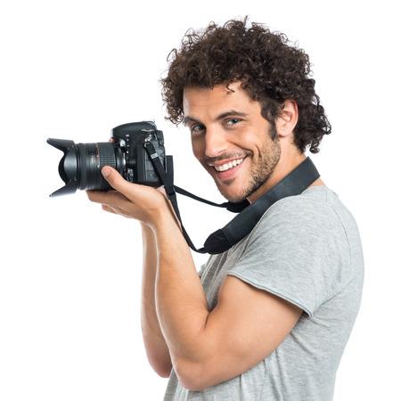 mládí: Mladý šťastný Fotograf drží kameru na bílém pozadí