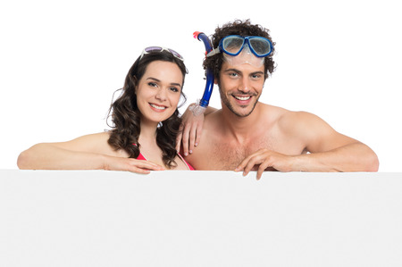 Happy Young Couple In Scuba Holding Empty Placard photo