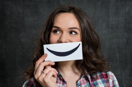 Young Woman Holding Smiley Emoticon Over Gray Background photo
