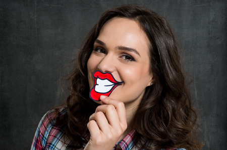 fake smile: Young Woman Holding Fake Paper Smile In Front Of Lips