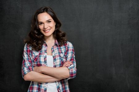 Glückliche junge Frau lächelnd mit Armcrossed über Blackboard mit Kopie Platz für Ihren Text Standard-Bild
