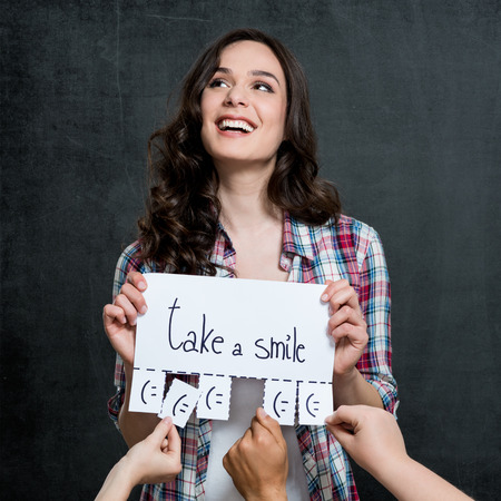 Young Happy Woman Holding Placard With Take A Smile Written On It photo
