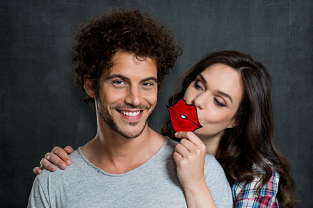 Young Happy Girl Kissing A Guy With Painted Red Lips Sign Over Gray Blackboard photo