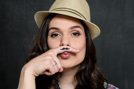 Portrait Of Young Woman In Hat With Painted Moustache Over Gray Background photo