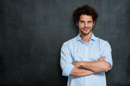 灰色の背景に満足している若い男の肖像