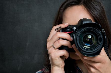 灰色の背景上のカメラを使用する若い女性のクローズ アップ