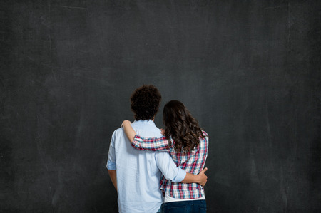 Young Couple Looking At Their Future Over Gray Background Ready For Your Product Or Text Banco de Imagens