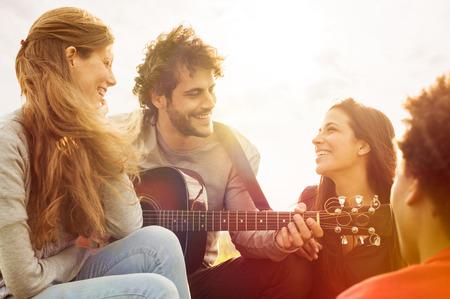 Feliz grupo de amigos disfrutando de la guitarra al aire libre de verano y cantando juntos