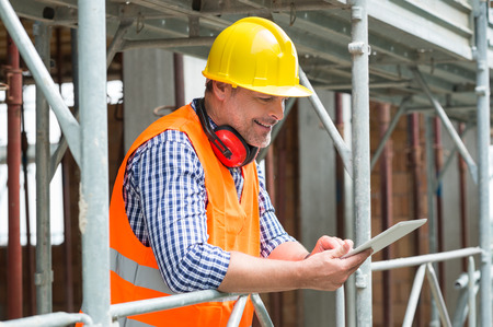 happy worker: Close-up Of A Happy Male Engineer Using Digital Tablet At Construction Site