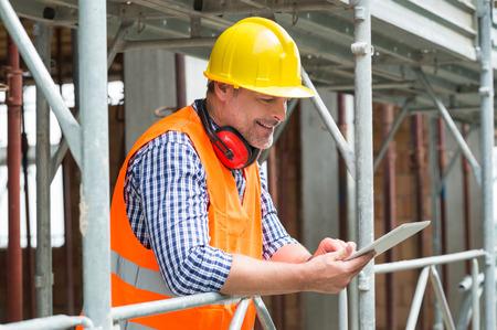 Close-up Van Een Gelukkig Man Engineer die Digitale Tablet Op Bouwplaats Stockfoto
